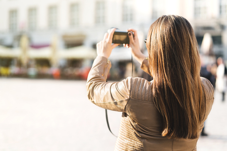 Tourist taking photo of town square during vacation with camera. Woman taking holiday picture in city. Tourism concept. Back view of female person.