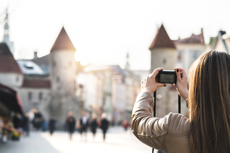 Woman in Tallinn taking photo of Viru Gate. Tourist on vacation taking picture of landmark in Estonia. People walking in popular street. Back view of girl with camera.