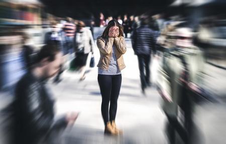 Ataque de pánico en lugar público. Mujer que tiene trastorno de pánico en la ciudad. Concepto de psicología, soledad, miedo o problemas de salud mental. Persona triste deprimida rodeada de gente caminando en una calle muy transitada. Foto de archivo