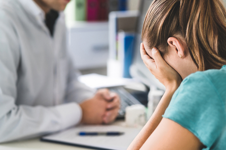 Sad patient visiting doctor. Young woman with stress or burnout getting help from medical professional or therapist. Anxiety, depression or mental health problems concept. Physician telling bad news.