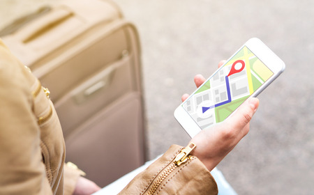 Tourist using map in phone app to navigate and find location of hotel in city. Woman with smartphone and luggage using GPS service. Travel and navigation concept.