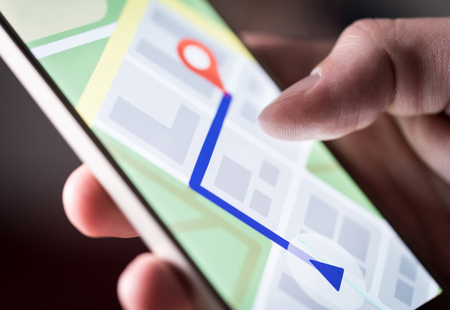 Map application in smartphone. Man navigating in city with mobile phone. Person using cellphone and searching hotel with navigation app. Macro close up of screen.