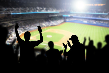 Baseball fans and crowd cheering in stadium and watching the game in ballpark. Happy people enjoying a match and sport event in arena. Friends watching ballgame live. Banco de Imagens