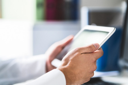 Doctor and medical professional using tablet at work in health care. Physician using digital electronic mobile device. Patient database online on the internet. Medic reading email in hospital office.