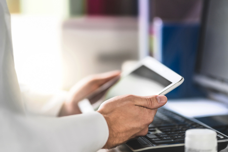 Doctor holding tablet in hand and reading medical record of patient. Physician using mobile device in office room. Digital and electronic modern technology in health care. Pharmacist with prescription