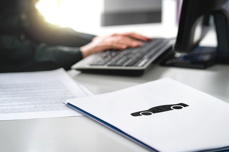 Woman writing car insurance document, bank loan application or lease contract. Car dealer working with computer in dealership. Buying or selling new or used vehicle online. Searching car on internet. Stock Photo