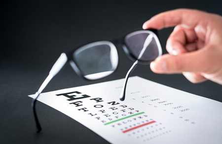 Optician holding glasses. Eyesight test chart in the background. Eye doctor fixing and repairing spectacles or lenses. Optometrist or ophthalmologist working in clinic. Stok Fotoğraf