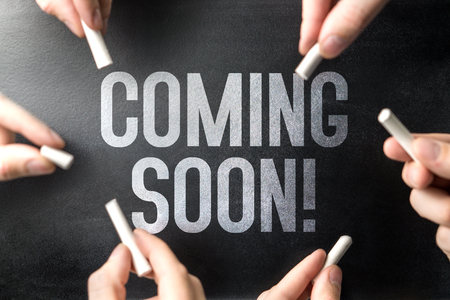 Coming soon text written on chalkboard sign and blackboard banner by many hands. Website or web page under construction or new announcement. Work in progress. Reklamní fotografie - 117447276