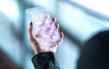 Transparent mobile phone. Futuristic glass smartphone. Cellphone with future digital technology screen display and interface. Business person holding invisible modern smart device.