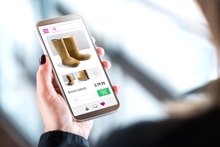 Female customer shopping in online fashion store with mobile phone. Woman buying shoes or boots with smartphone. Internet sale on website in cellphone.