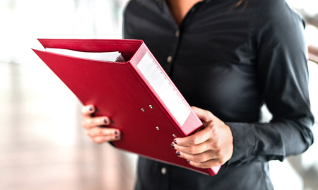 Professional business woman holding folder full of paper documents. Lawyer, legal adviser, office assistant or company manager with binder. Banco de Imagens - 117412807