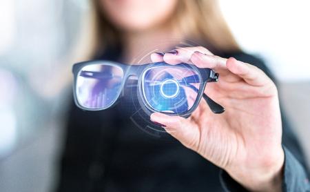 Gafas inteligentes de pantalla virtual con interfaz futurista de alta tecnología. Mujer sosteniendo gafas con interfaz nanotecnológica. Visión de realidad aumentada con gafas modernas. Innovación futura con IOT y VR.