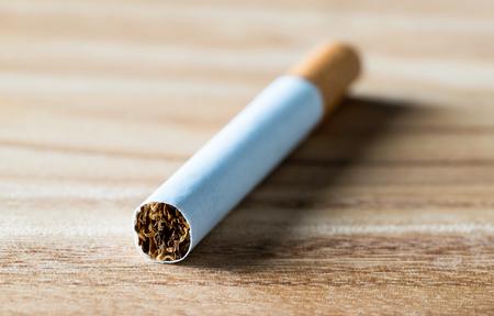 Zigarette auf Holztisch, Makro Nahaufnahme. Tabak, Papier und Nikotin. Hör auf zu rauchen.