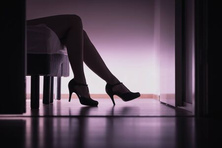 Escolta, o nena de azúcar acostada en la cama con piernas largas y tacones altos. Concepto de prostitución, trabajo o citas de azúcar. Stripper o mujer pagada. Cuerpo erótico en dormitorio.