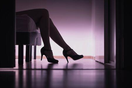 Escorte, ou babe en sucre allongée sur le lit avec de longues jambes et des talons hauts. Concept de prostitution, de travail ou de rencontre avec le sucre. Strip-teaseuse ou femme payée. Corps érotique dans la chambre.