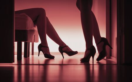 Two sexy ladies in high heels. Women having sex. Lesbians, prostitutes or escorts. Long legs silhouette in red light. Sexual glamour lingerie models. Laying on bed. Home bedroom, hotel or brothel. Stock Photo
