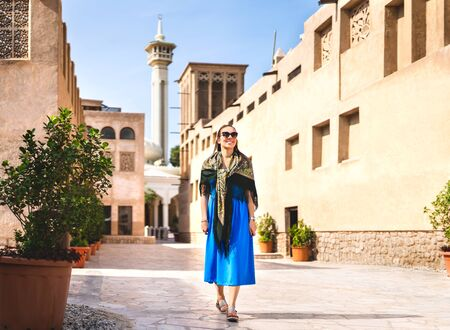 Woman walking in old Dubai, UAE. Traditional Arab street and mosque. Female tourist in historical Al Fahidi neighbourhood wearing dress. Tourism in heritage district. Happy vacation lifestyle.