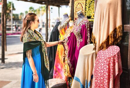 Woman in souk. Tourist looking at traditional Arabian dresses and clothes in store or outdoor market. Lady customer shopping souvenir in old Dubai. Tourism and vacation in the United Arab Emirates.