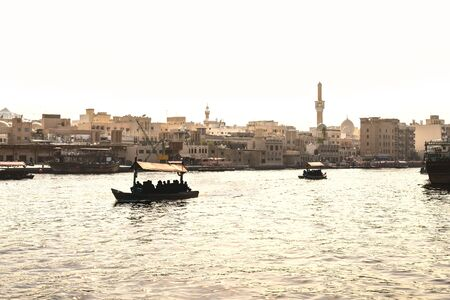 Dubai Creek with abra boats. Local people and tourists using water taxi and ferry in old town river. Traditional cruise. Scenic Arabian city view with mosque and buildings. Historical district in UAE.