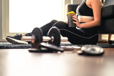Fitness woman drinking protein or recovery drink after workout and weight training. Working out and exercise at home. Lady in sportswear holding shaker. Dumbbell and gym equipment on the floor.