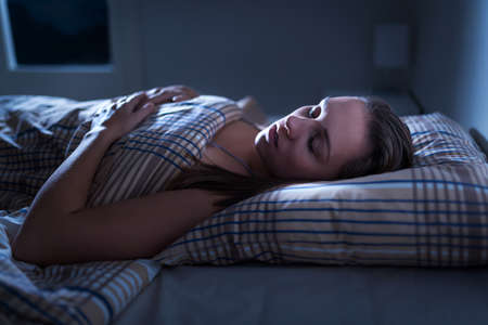 Calm and peaceful woman sleeping in bed in dark bedroom. Lady asleep at home in the middle of the night. Pillow, blanket and moonlight. Nightmare or sleep apnea concept. 版權商用圖片