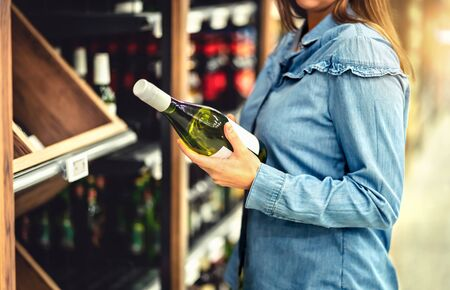 Customer buying white wine or sparkling drink. Alcohol aisle in store or supermarket. Woman holding bottle. Buying riesling or chardonnay. Shelf full of drink choices. Shopping spirits.
