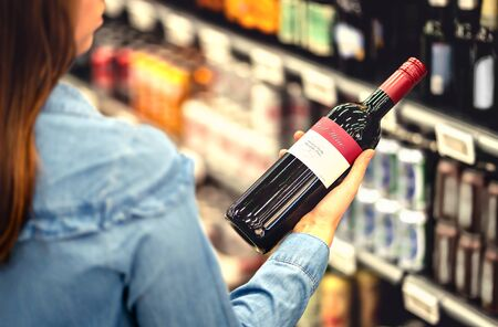 Woman reading the label of red wine bottle in liquor store or alcohol section of supermarket. Shelf full of alcoholic beverages. Female customer holding and choosing a bottle of merlot or sangiovese.