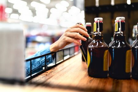 Customer taking bottle of beer from shelf in liquor store. Woman shopping alcohol or supermarket staff filling and stocking shelves in drink aisle. Cider, lager or dark. Retail worker doing inventory.