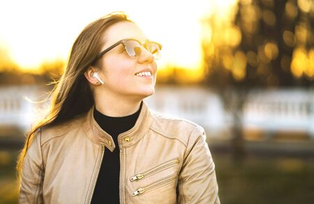 Wireless headphones, earbuds. Woman listening to music with earpods in a park. Happy young lady smiling. Sunglasses and leather jacket. Positive girl using modern audio technology outdoors at sunset.