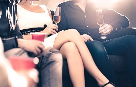 Friends talking at a party. Stylish trendy people drinking champagne and having a conversation. Couple, well dressed man and woman sitting on couch flirting. Fun luxury lifestyle. Weekend gathering. Reklamní fotografie - 141630976