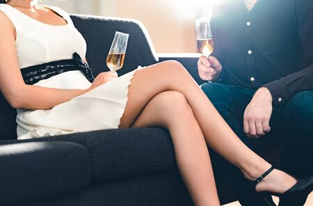 Elegant woman with sexy legs flirting with a stylish man on a date. Couple talking and drinking champagne on couch. Well dressed rich wealthy people dating on a glamorous evening. Fancy luxury party.