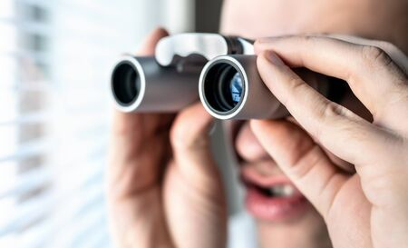 Nosy neighbor or stalker with binoculars. Funny crazy man staring at people. Curious guy looking out the window. Silly face. Snooping and searching rumour or gossip. Peeping tom, pervert or voyeur. 스톡 콘텐츠