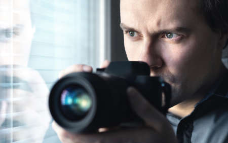 Private detective, undercover cop, investigator, spy or paparazzi with camera taking photos. Agent or police spying, investigating or following people. Espionage or surveillance concept. Man hiding. Reklamní fotografie - 157583289