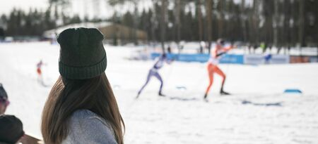 Fan cheering in skiing competition. Winter world championship ski event. Woman watching cross-country skier competing in stadium. Crowd supporting athlete. Stock Photo