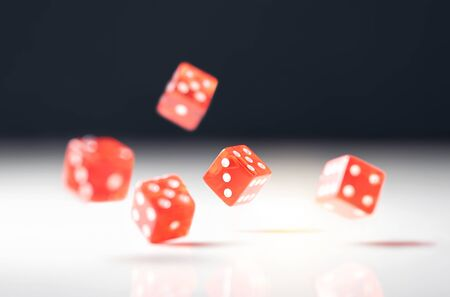 Roll the dice. Risk, luck, gambling, betting or addiction concept. Throwing five red casino and poker dice on table.