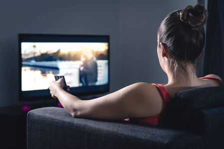 Woman streaming movie or watching series. Person using smart tv remote control to choose film or change channel. Stream or video on demand (VOD) service in television screen. Digital entertainment.