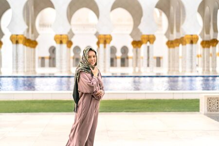 Happy female tourist wearing scarf and dress in The Mosque in Abu Dhabi. Smiling woman walking in beautiful building with water and traditional Muslim decor. Vacation and travel.