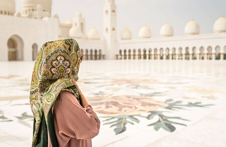 Back view of Woman in The Mosque. Traditional Muslim building in the United Arab Emirates. Female visitor wearing headscarf. Tourism and vacation in Abu Dhabi. Girl travel in UAE.