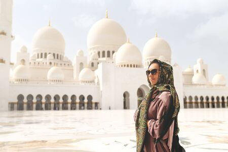 Happy woman in The Sheikh Zayed Grand Mosque. Female tourist with headscarf and dress in Adu Dhabi. Lady walking in traditional Muslim building with beautiful islamic decor in Abu Dhabi, UAE.