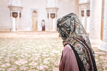 Woman in Muslim prayer room in mosque. Young lady wearing headscarf. Traditional carpet and Arab architecture. Islam religion and tourism concept. Back view female visitor. 스톡 콘텐츠