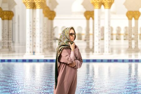 Woman in grand mosque of Sheikh Zayed in front of water. Islamic decor. Female tourist in muslim country. Tourism, travel and people on vacation in Abu Dhabi, United Arab Emirates (UAE) concept. 스톡 콘텐츠