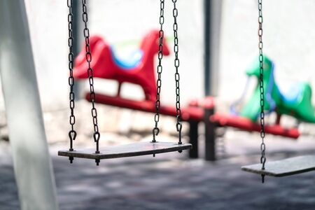 Empty swing at a playground. Sad dramatic mood for negative themes such as bullying at school, child abuse, pedophilia, traumatic childhood or kidnap. Seesaw in the background. Old retro vintage feel.