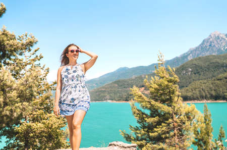 Woman walking in nature, mountain in the background. Adventure, freedom and carefree lifestyle. Millennial lady in summer dress. Landscape with valley, lake and forest. Candid smiling happy person.