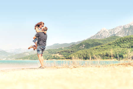Man lifting woman in the air. Happy laughing couple on holiday. Mountain landscape. Boyfriend carrying girlfriend. Romantic moment after proposal or engagement. Passionate lovers on summer vacation. Banco de Imagens