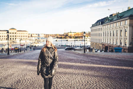 Stockholm in winter. Person walking in urban city street in Sweden. Happy tourist looking at buildings in the old town. Woman in Gamla Stan. Tourism and vacation in Scandinavia. Travel lifestyle.
