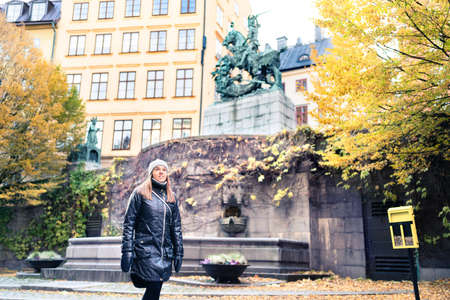 Person walking in Stockholm and old town (Gamla Stan) in winter or autumn. Yellow fall colors in trees and leafs. Woman on vacation in Sweden in Scandinavia. Beautiful happy tourist in Swedish city. Stock fotó