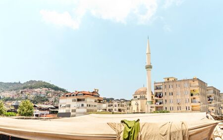 Old town view in Alanya, Turkey with tent in outdoor market place, minaret, mosque and local buildings. Traditional Turkish culture and Islam in the city. Urban cityscape and marketplace in europe. Banque d'images