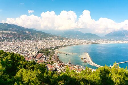 Alanya Turkey aerial view. Panorama cityscape and landscape of the Turkish city and riviera in summer. Tourist attraction and holiday destination. Mountain, harbour and the Mediterranean Sea.