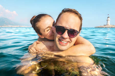 Couple taking selfie in water while swimming in the sea on holiday. Two happy people on fun family vacation. Romantic honeymoon in tropical summer paradise. Girlfriend hugging, boyfriend laughing. Stock fotó