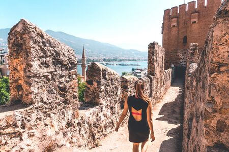 Traveler exploring the city of Alanya in Turkey. Woman walking and discovering old landmark in Europe. Tourist sightseeing in the Red Tower. Travel lifestyle, wanderlust and freedom. Summer vacation.